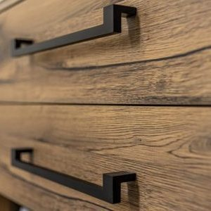Wooden chest of with drawers with black handles close up.